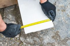 The process of measuring the length of a sheet of drywall. Using a roulette Royalty Free Stock Photos