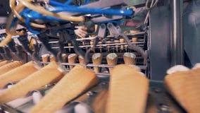 Process of mechanical relocation of ice-cream cones onto the conveyor belt. 4K stock video