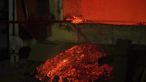 The process of melting metal at the plant in the furnace. Workers remove the slag, to obtain a pure alloy. Metallurgical production stock footage