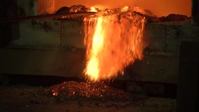 The process of melting metal at the plant in the furnace. Workers remove the slag, to obtain a pure alloy.