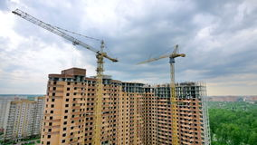 The process of multi-storey house construction. Timelapse. The process of multi-storey house construction. Two cranes. Time lapse stock video