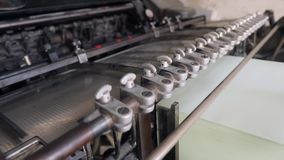 Process of Offset Print on Vintage Old Printing Conveyor Machine in Retro Style Typography. 4K. Process of Offset Print on Vintage Old Printing Conveyor Machine stock video footage