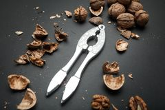 The process of opening the core of the walnut and whole walnuts on a black background stock image