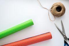 Process of package and wrapping Christmas and New Year gift box. Wrapping paper, scissors, twine on the white background. Royalty Free Stock Photography