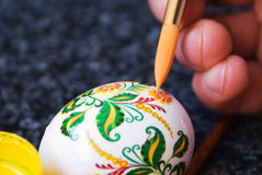 Process of painting of easter egg. A hand with a brush paints a lying in other hand easter egg Royalty Free Stock Photography