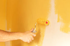 The process of painting the walls in yellow color Stock Image
