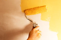 The process of painting the walls in yellow color Royalty Free Stock Image