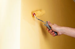 The process of painting the walls in yellow color Stock Photo