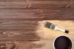 Process of painting the wood boards with the brush and the brown Royalty Free Stock Photography