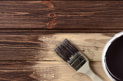 Process of painting the wood boards with the brush and the brown Stock Image