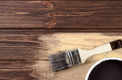 Process of painting the wood boards with the brush and the brown Royalty Free Stock Photos