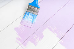 Process of painting the wood boards with brush and violet color. Process of painting the pine wood boards with the brush and the light violet color Royalty Free Stock Photo