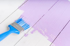 Process of painting the wood boards with brush and violet color. Process of painting the pine wood boards with the brush and the light violet color Royalty Free Stock Photography