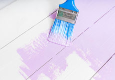 Process of painting the wood boards with brush and violet color. Process of painting the pine wood boards with the brush and the light violet color Stock Image