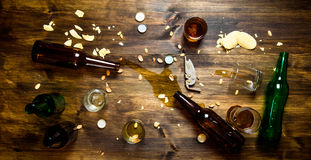 Process of party - spilled beer, bottle caps Royalty Free Stock Photo