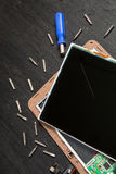 Process of PC Tablet device repair near screwdriver and bit on black wooden background. Disassembled. Broken glass, screen destroy. Ed. Copy space stock images