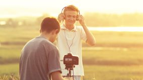 Process of photo and video shooting in a field in nature, man making video of guy posing as model in headphones at sunset royalty free stock photos