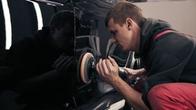 Process of polishing black newcar with professional mashine. Man in red onepiece worksuit working hard. stock video footage