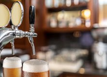 The process of pouring beer into the glass. Stock Photography