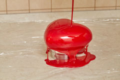 Process of pouring red glaze on heart shape form cake Royalty Free Stock Photography