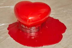 Process of pouring red glaze on heart shape form cake Royalty Free Stock Images