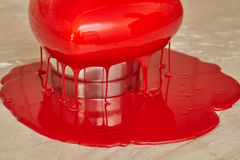 Process of pouring red glaze on heart shape form cake Royalty Free Stock Photo