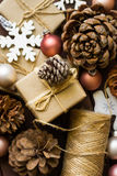 Process of praparing and wrapping Christmas and New Year gits, natural materials, craft paper, twine, pine cones, wood ornaments Royalty Free Stock Images