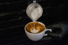 Process of preparation of a cappuccino with latte art. Work the barista in coffee shop. Black background and gloves. Fresh coffee stock photography