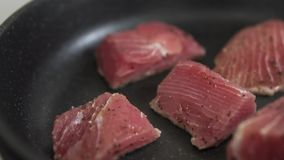 Process of preparation fresh tuna. Roasting fillet of tuna. Slow motion closeup. Closeup fresh fillet. Healthy food. Roasting in a hot frying pan with salt and stock video footage