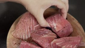 Process of preparation fresh tuna. Slow motion closeup. Closeup fresh fillet. Healthy food. Woman roasting fillets tuna with salt and papper. Big steaks of red stock video footage