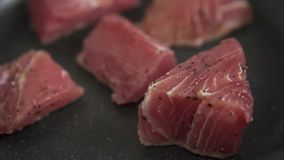 Process of preparation tuna steak. Roasting fillet of tuna. Slow motion closeup. Closeup fresh fillet. Healthy food. Roasting in a hot frying pan with salt and stock video
