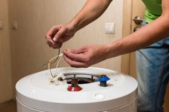 Master hands hold wires of water heater. Process of repair old boiler with rust and corrosion royalty free stock image