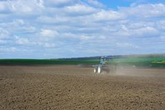 The process of spreading a mineral granulated fertilizer with an aggregate attached to a tractor.  Stock Photos