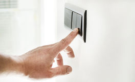 The process of turning on the light. By a switch on the wall stock photography