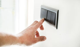 The process of turning on the light. By a switch on the wall stock images