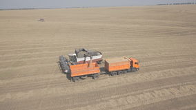 Process of unloading combine hopper into back of a truck on field. When grain hopper of machine is filled, it pulls truck with a trailer and unloads in his stock video footage