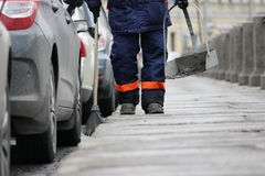 Process of urban street cleaning sweeping. Worker with broom and dust pan Royalty Free Stock Photo