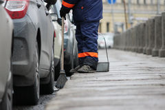 Process of urban street cleaning sweeping. Worker with broom and dust pan Stock Photo