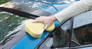 The process of washing a blue car with the help of shampoo and s. The process of washing a blue car with the help of shampoo and yellow sponges in the yard Royalty Free Stock Photo