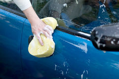 The process of washing a blue car with the help of shampoo and y Royalty Free Stock Photos