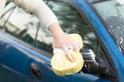 The process of washing a  car with the help of shampoo and  spon. The process of washing a blue car with the help of shampoo and yellow sponges in the yard Royalty Free Stock Image