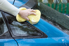 The process of washing a  car with the help of  sponges. The process of washing a blue car with the help of shampoo and yellow sponges in the yard Royalty Free Stock Image
