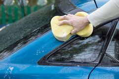 The process of washing a car with the help of  yellow sponges. The process of washing a blue car with the help of shampoo and yellow sponges in the yard Royalty Free Stock Photos