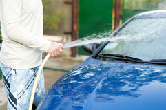 The process of washing cars with a hose with water Stock Images