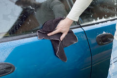 The process of washing and wiping cars with the help of a cloth. In the yard Stock Image