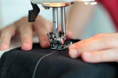 Processar av att sy Linum på symaskinen syr symaskinen Linum för händer för kvinna` s symaskin- och kvinnligfingrar ut ur Arkivbilder