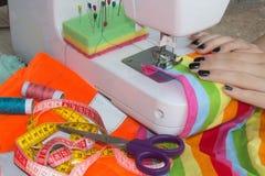 Processar av sömnaden på symaskinen syr den kvinnliga handsymaskinen symaskin- och kvinnligsax Royaltyfri Bild