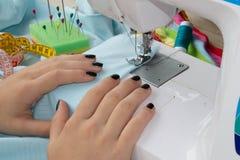 Processar av sömnaden på symaskinen syr symaskinen för händer för kvinna` s kvinnaskräddare som dragar lädermaterial på sömnadmac Arkivbild