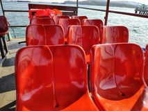 Red chairs lined up on passenger boat. stock image