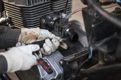 Processen av att att bry sig och underhåller en gammal motorcykel som är retro Arkivfoto